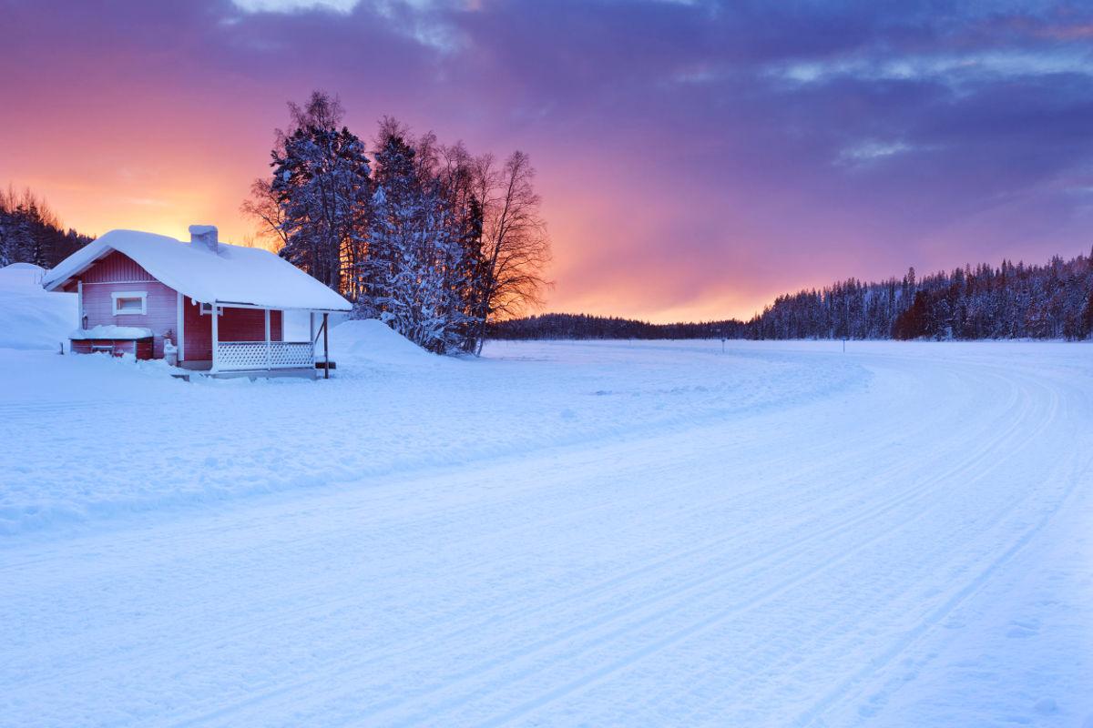 Ein kleines Haus in der verschneiten, idyllischen Landschaft Lapplands.
