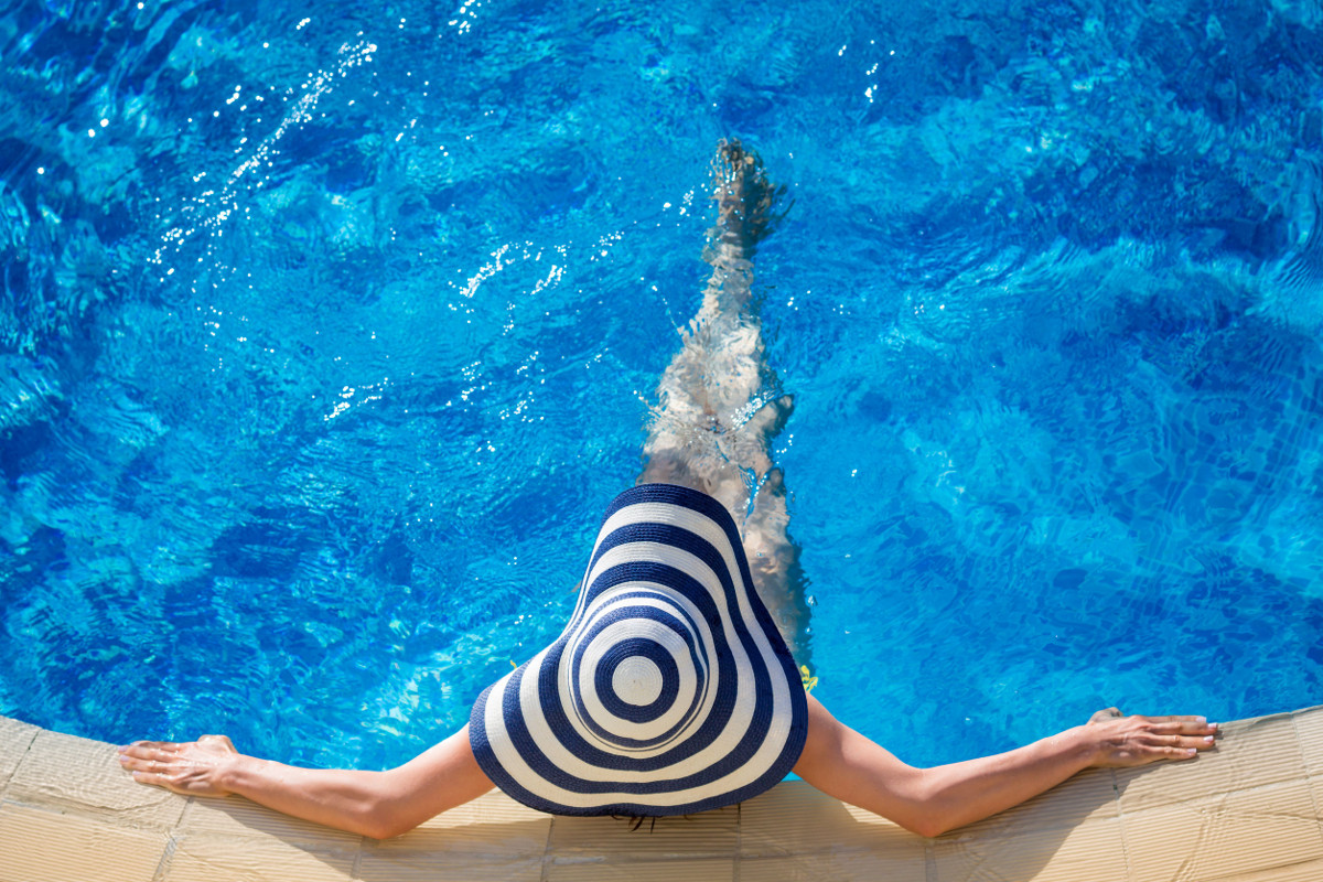 Young woman in swimming pool. Summer vacation concept // Frau entspannt am Swimmingpool.