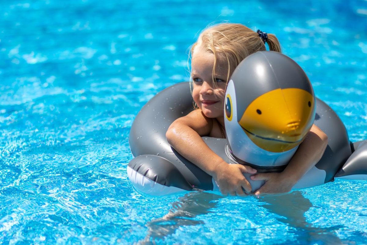 Mädchen badet im Pool mit einem aufblasbaren Schwimmring.
